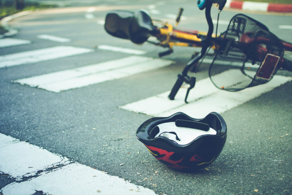 Helmet and bike lying on the road on a pedestrian crossing.